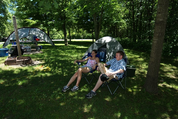 a couple sitting in front of their tent in the campground