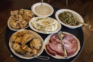 Fried chicken, mashed potatoes, ham, green beans and gravy on a serving tray