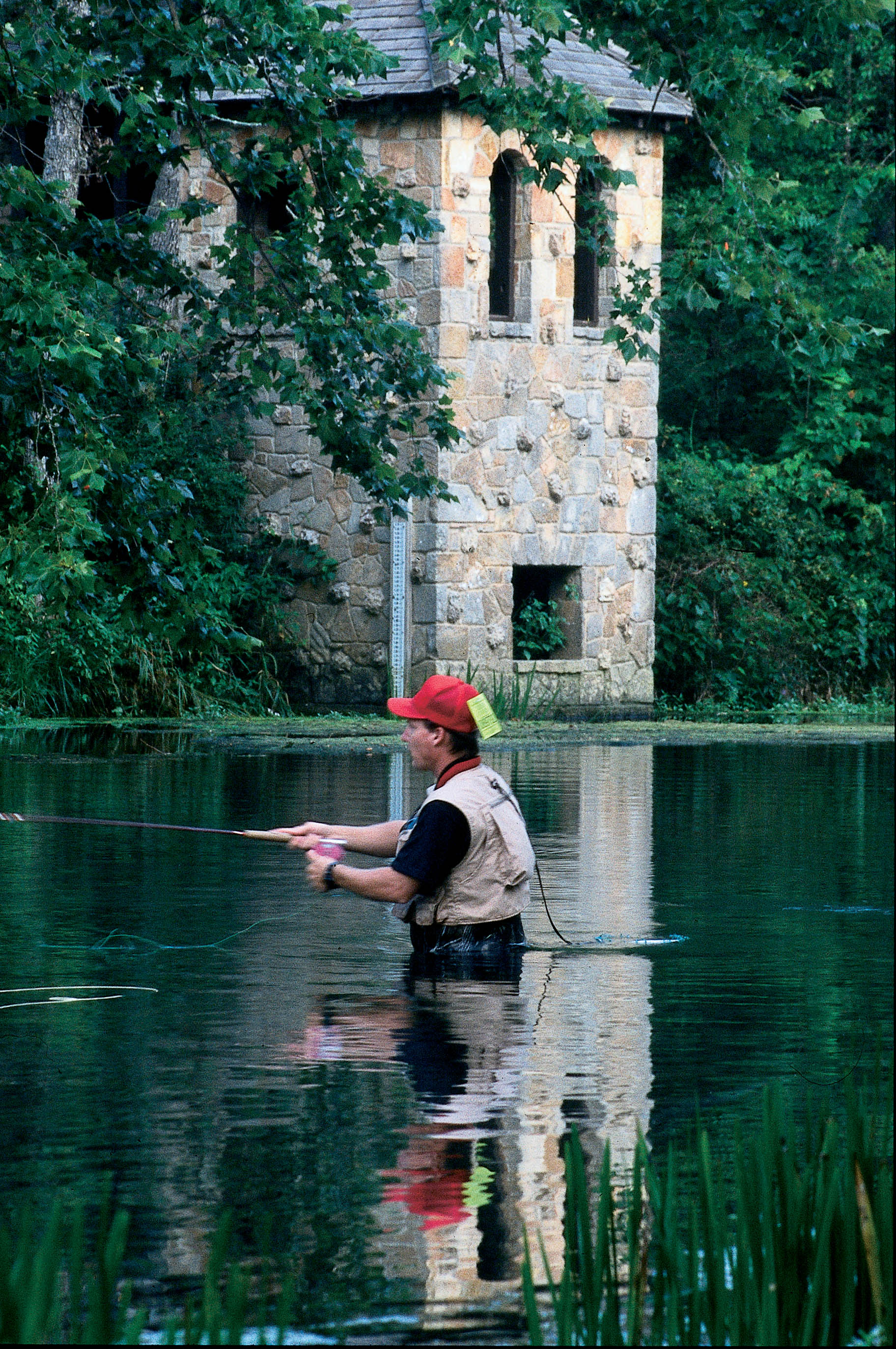 A man wading in the water fishing in front of one of the historic structures at Bennett Spring State Park
