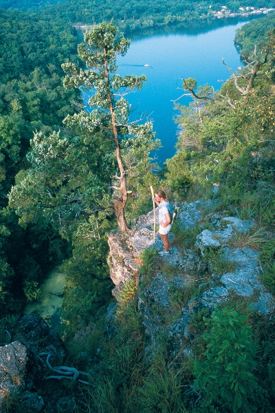 Hiker standing on a bluff overlooking the Lake of the Ozarks