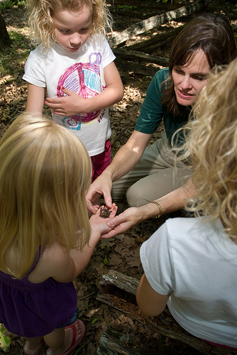 a naturalist showing a group of kids somethingin her hand