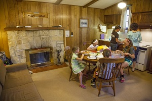a family eating at the table inside one of the cabins, which has a fireplace