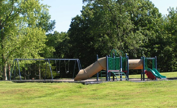 playground equipment with two small slides and a swing set