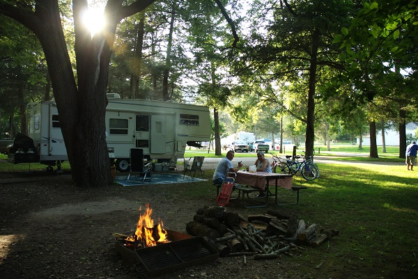 Couple sittling at picnic table in front of their camper with a campfire in the foreground
