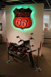 a motorcycle stands below a Phillips 66 sign inside the visitor center