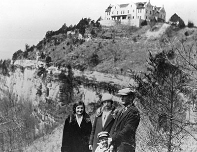 Historic photo of a family standing below the bluff where the Ha Ha Tonka castle is